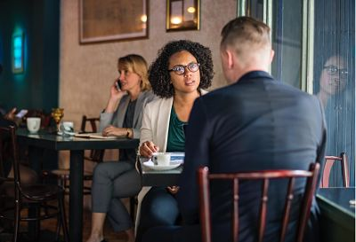 woman in eyeglasses speaking with man in cafe